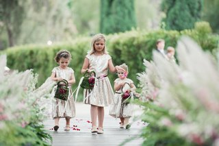 flower-girls-in-gold-dresses-and-moss-purses-with-pink-flowers-outside