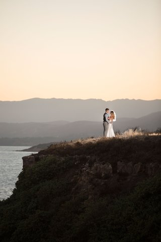 bride-and-groom-couple-location-portrait-shot-reception-hair-down-sleek-dress-on-cliff-in-california