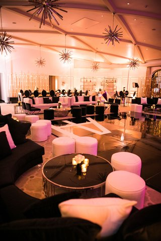 wedding-reception-ballroom-for-dancing-black-white-lounge-furniture-gold-metallic-elements-ottomans