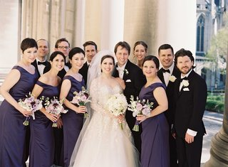bridal-party-purple-black-outside-roman-catholic-church-bridesmaids-groomsmen-dresses-suits-classic