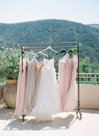 monique-lhuillier-wedding-dress-and-pink-and-taupe-bridesmaid-dresses-bhldn-on-clothes-rack-view