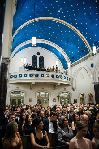 wedding-guests-facing-altar-at-church-wedding-ceremony-traditional-houston-texas-bright-blue-ceiling