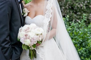 a-bride-and-groom-standing-together-while-the-bride-holds-a-bouquet-of-ivory-and-blush-rose-ranuncul