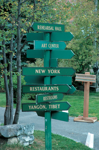 green-sign-with-arrows-pointing-toward-different-cities