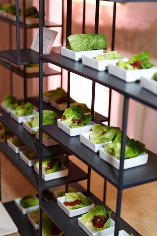 wedding-cocktail-hour-with-romaine-lettuce-leaves-in-square-dishes-on-black-stand