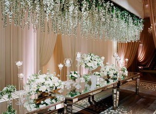 mirror-table-with-white-flower-and-greenery-installation-over-table-white-rose-escort-card-table
