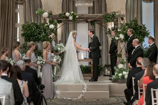 bride-and-groom-laughing-during-their-ceremony-indoor-ceremony-with-wooden-chuppah-cathedral-veil