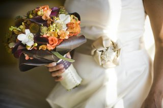 bride-holding-purple-green-and-orange-autumn-flowers