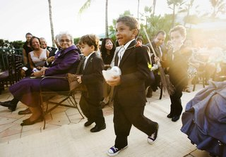 three-ring-bearers-walk-down-aisle-with-pillow-and-broom