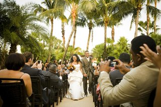 african-american-bride-and-groom-walk-up-aisle-guests-take-photos
