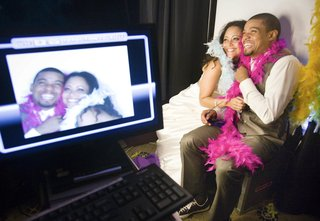 bride-and-groom-with-pink-and-white-feathers-in-front-of-photobooth