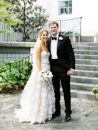 bride in strapless mira zwillinger wedding dress flower appliques and groom in tuxedo nashville
