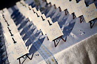 wedding-guest-place-cards-are-set-on-miniature-easels