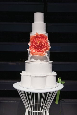 wedding cake tall white pearl dog with sugar flower peony design in center cut after ceremony