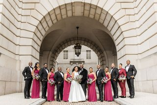 bridesmaid in a line wedding dress groom in velvet tuxedo jacket bridesmaids in fuchsia magenta dress and suit