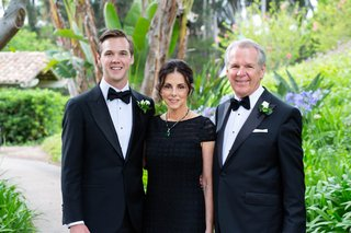 wedding photo of groom with  mother of groom in black dress emerald necklace and father of groom tuxedo