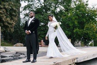 bride-in-long-sleeve-wedding-dress-cathedral-veil-updo-walking-toward-groom-long-tail-tux-first-look
