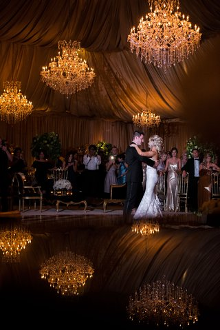 wedding-reception-first-dance-on-reflective-dance-floor-chandeliers-hanging-from-top-of-tent