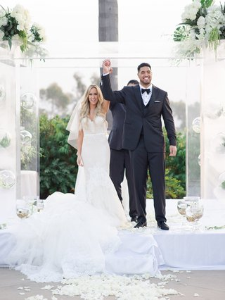 bride-in-wedding-dress-with-groom-levine-toilolo-atlanta-falcons-football-player-hands-in-air