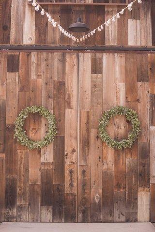 green-leaf-wreath-decor-on-rustic-vintage-barn-doors-at-winery-vineyard-wedding-reception-location