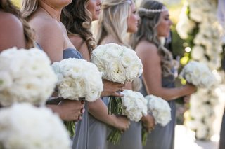 bridesmaids-in-grey-blue-periwinkle-dresses-strapless-holding-white-bouquets-in-line-processional