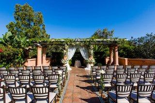 wedding-ceremony-outdoors-tile-floor-trellis-greenery-white-chuppah
