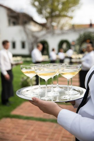 wedding-reception-welcome-drink-champagne-in-glass-coupe-glass-on-silver-tray-walkway-to-reception
