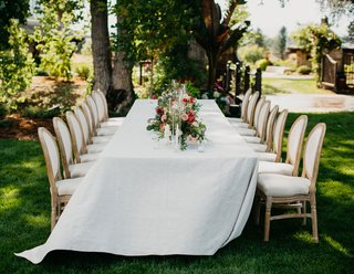 wedding-reception-garden-setting-white-linen-french-upholstered-chairs-low-garden-centerpiece-flower
