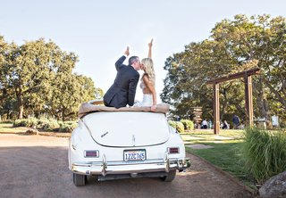 bride-and-groom-in-vintage-convertible-packard-car-white-with-peace-signs-on-back-of-seat