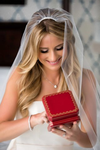 bride-in-strapless-wedding-dress-bracelet-veil-necklace-opening-red-jewelry-box