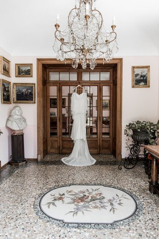 wedding-dress-hanging-up-on-door-frame-in-italy-switzerland-villa-ornate-decor
