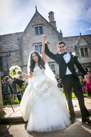 bride-and-groom-holding-hands-celebrating-after-outdoor-ceremony-at-mansion-in-pittsburgh-white