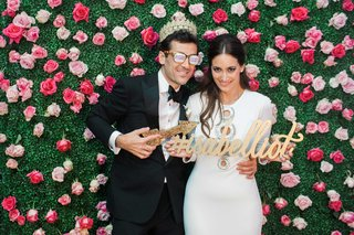 groom-in-hashtag-sunglasses-with-crown-and-bride-in-after-party-dress-with-hashtag-sign-photo-booth