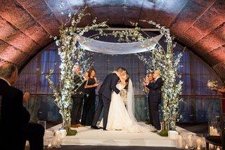 wedding-ceremony-granite-arch-greenery-white-flower-chuppah-tallit-bride-and-groom-parents-jewish