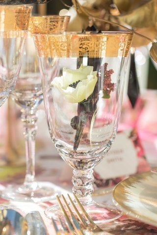 small-white-flower-inside-glass-wine-glass-with-gold-detailing-around-gold-flatware