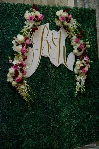 gold-monogram-on-white-border-hedge-wall-greenery-backdrop-photo-booth-pink-white-burgundy-flowers