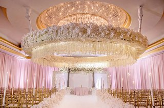 wedding-ceremony-circle-flower-ceiling-arrangement-gold-chairs-pink-lighting-drapery-white-flowers