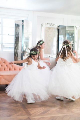 three-flower-girls-in-tulle-dresses-white-shoes-flower-crowns-bows-dancing-on-wood-floor
