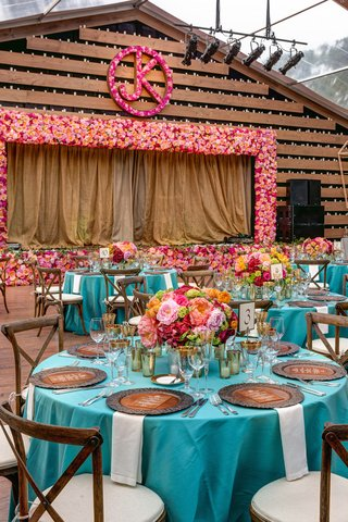 wedding-reception-with-a-wood-stage-framed-by-pink-and-orange-flowers-pink-flower-initials