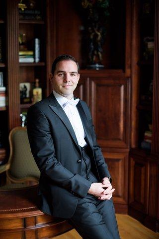 groom-in-gibeon-tolbert-tuxedo-in-office-leaning-against-desk