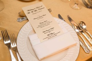 champagne-colored-menus-on-white-plates-on-gold-table-linens