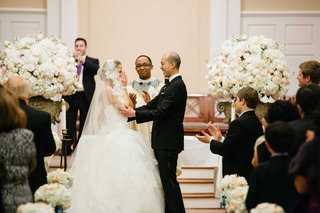 bride-and-groom-at-altar-of-church-with-white-and-blush-wedding-flower-decorations