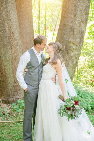 couple-embrace-each-other-gray-suit-white-wedding-dress-celtic-wedding-green-and-red-bouquet-veil