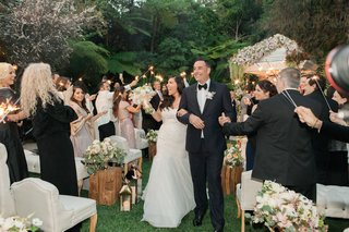 bride-in-monique-lhuillier-and-groom-walking-up-aisle-at-hotel-bel-air-sparklers-waved-by-guests