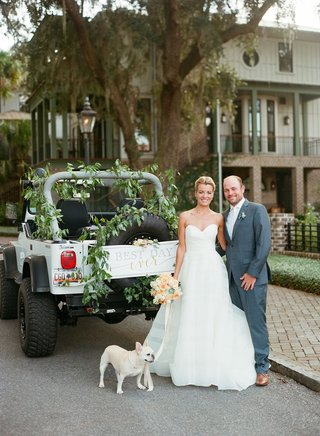 bride-in-strapless-wedding-dress-with-groom-in-grey-suit-jeep-wrangler-french-bull-dog-greenery