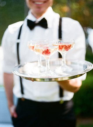 server-in-suspenders-and-bow-tie-holding-silver-tray-coupe-glass-champagne-with-raspberry-fruit-red