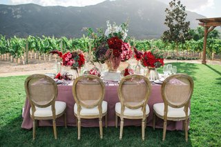 pink-table-linens-red-dark-purple-floral-arrangements-and-gold-and-tan-chairs-rustic-wedding