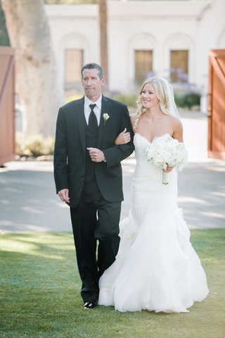 bride-in-a-strapless-hayley-paige-dress-and-white-bouquet-walks-down-the-aisle-with-father