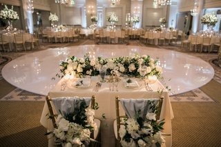 sweetheart-table-in-front-of-round-dance-floor-chiavari-chairs-with-blue-fabric-and-florals