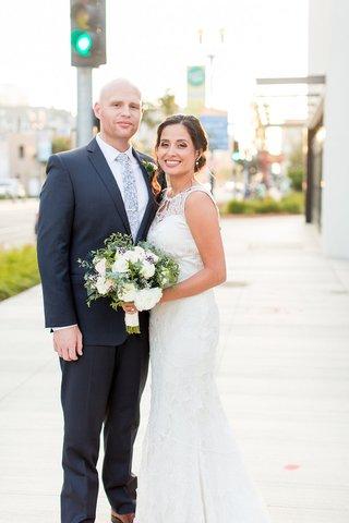 wedding-portrait-on-street-sidewalk-in-long-beach-bride-in-claire-pettibone-wedding-dress-groom-suit